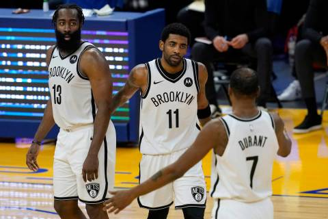 Brooklyn Nets guard Kyrie Irving, middle, gathers with guard James Harden (13) and forward Kevi ...