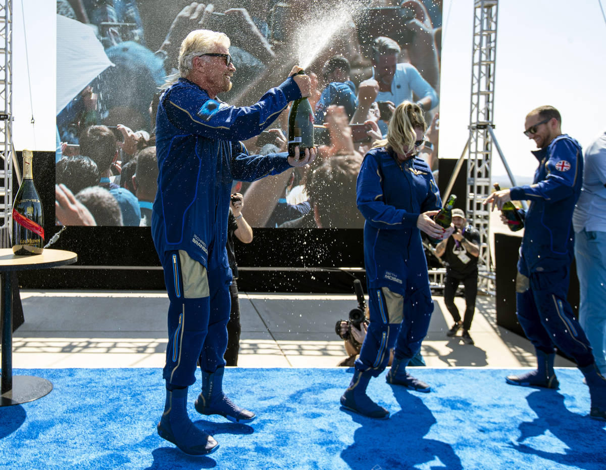 Virgin Galactic founder Richard Branson, left, sprays champagne to crew members Beth Moses and ...