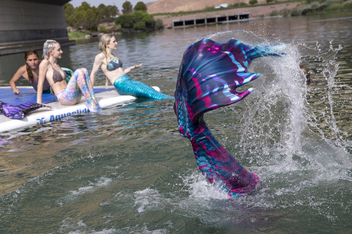 Mermaids sun themselves and splash around at Lake Las Vegas on Saturday, June 19, 2021, in Hend ...
