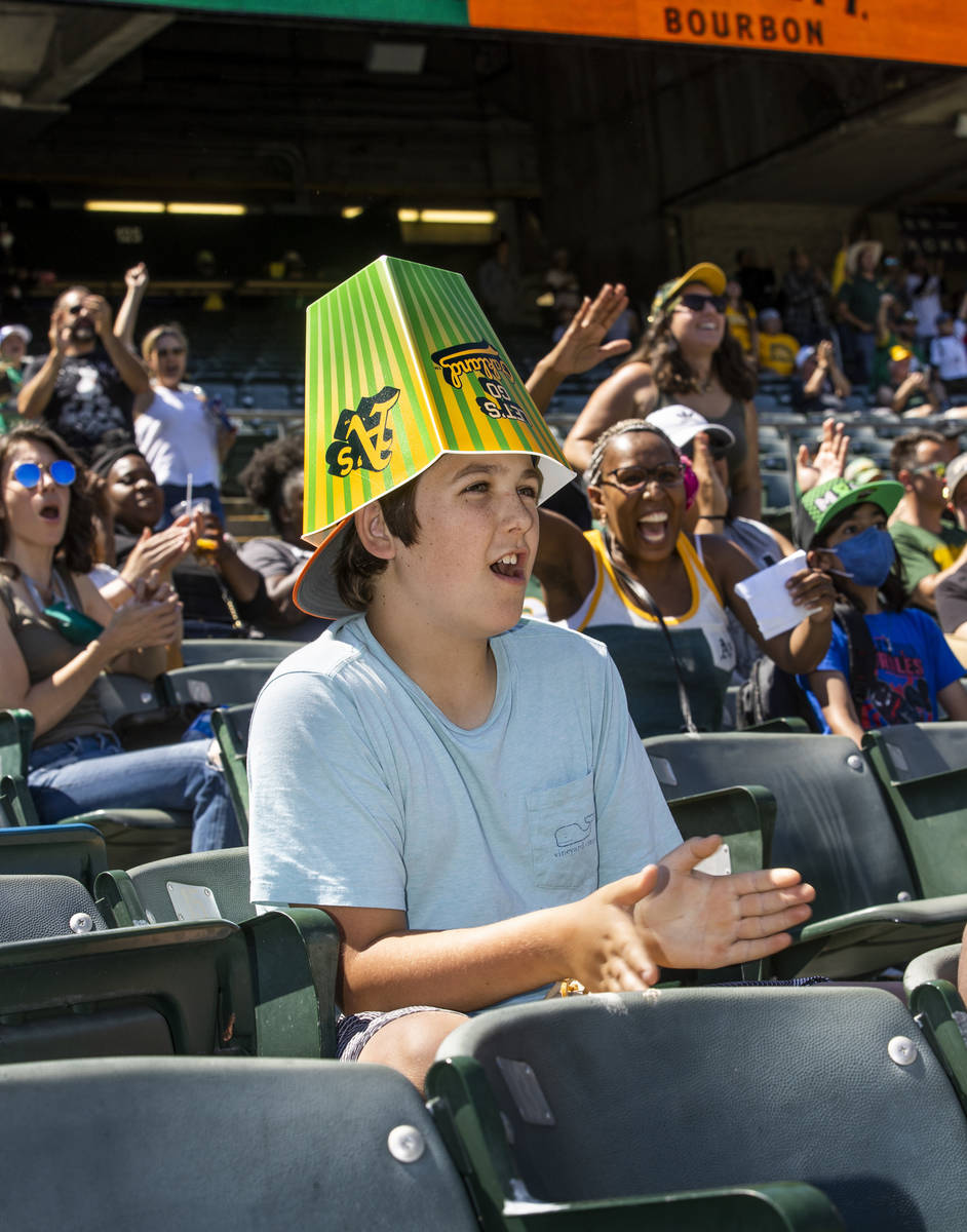 Oakland A's fan Sheb Bellias, 12, cheers with an empty popcorn container on his head while pl ...