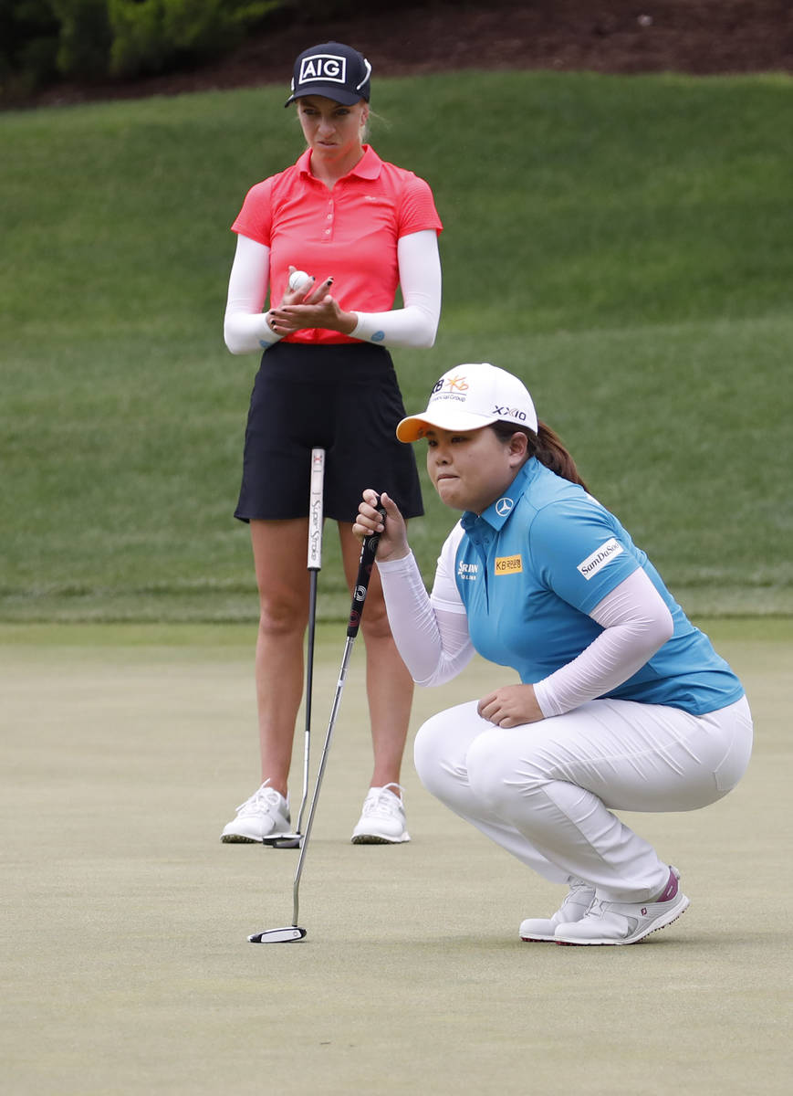 Inbee Park, foreground, lines up a putt on the 15th green during the fourth round of the Bank ...
