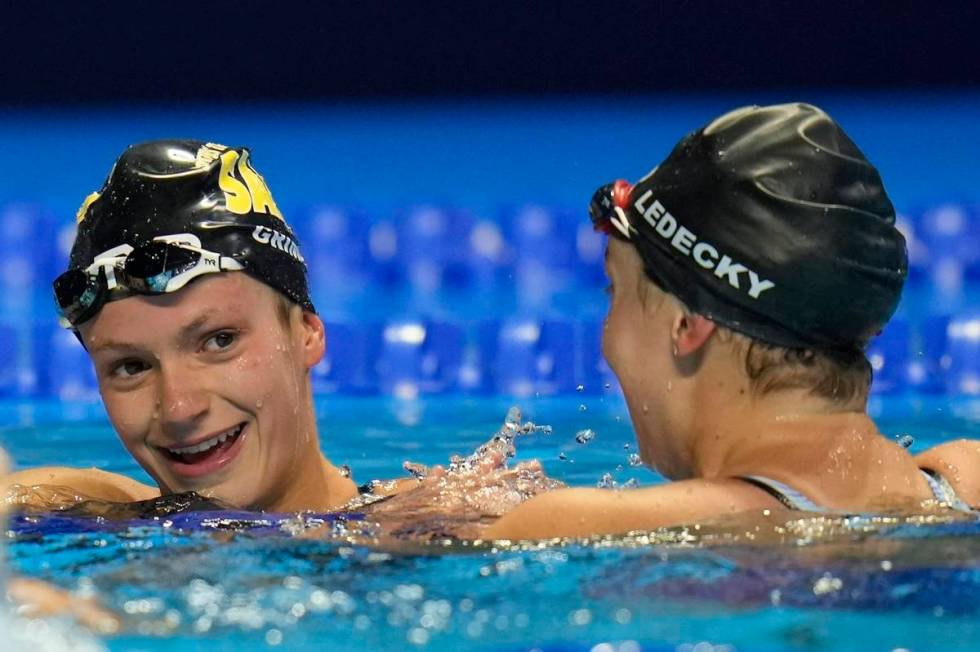 FILE - Katie Ledecky congratulates Katie Grimes after the women's 800 freestyle during wave 2 o ...