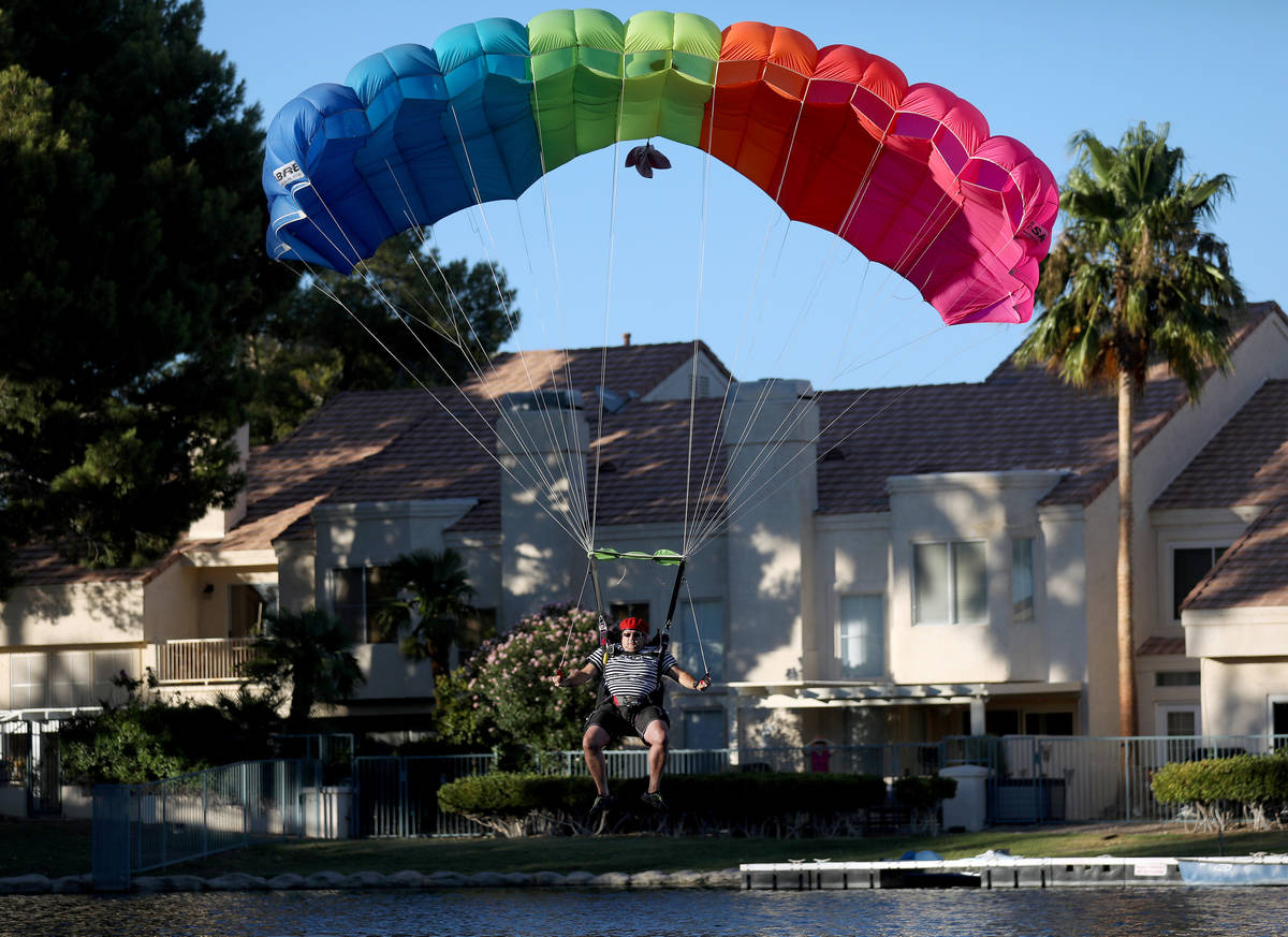 A skydiver descends from a plane for Marché Bacchus' Bastille Day celebration, in front of the ...