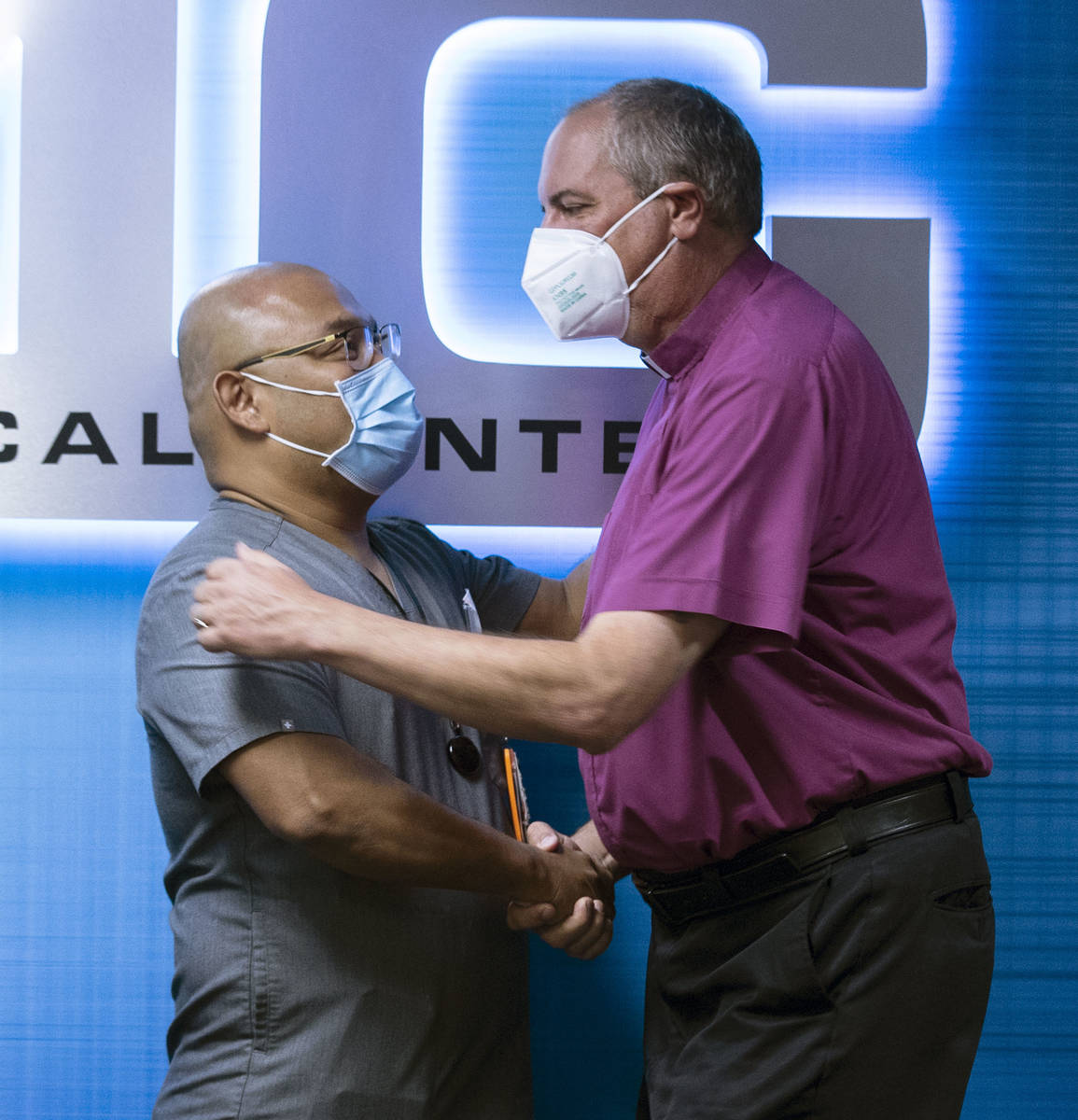 The Rev. Russ Smethers, right, a local pastor who was stabbed 21 times on March 8, shakes hands ...