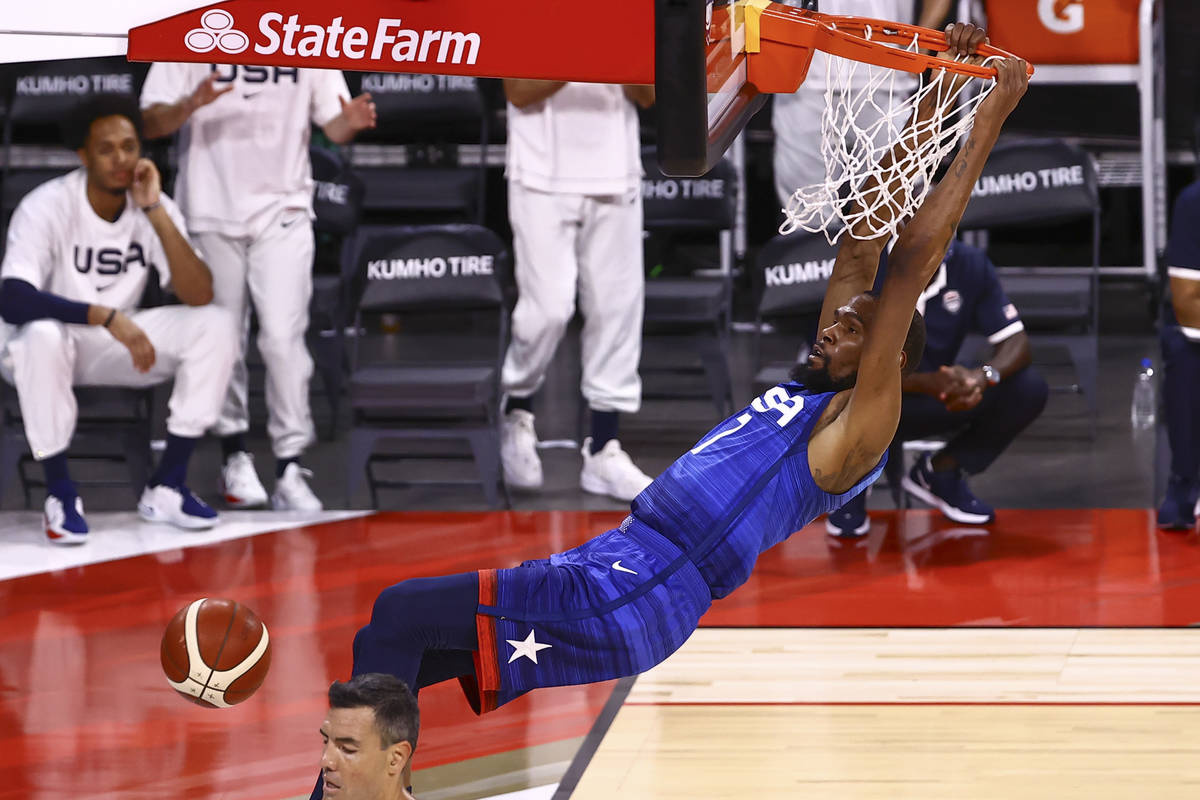 USA's Kevin Durant (7) dunks the ball over Argentina's Luis Scola during the first half of an e ...