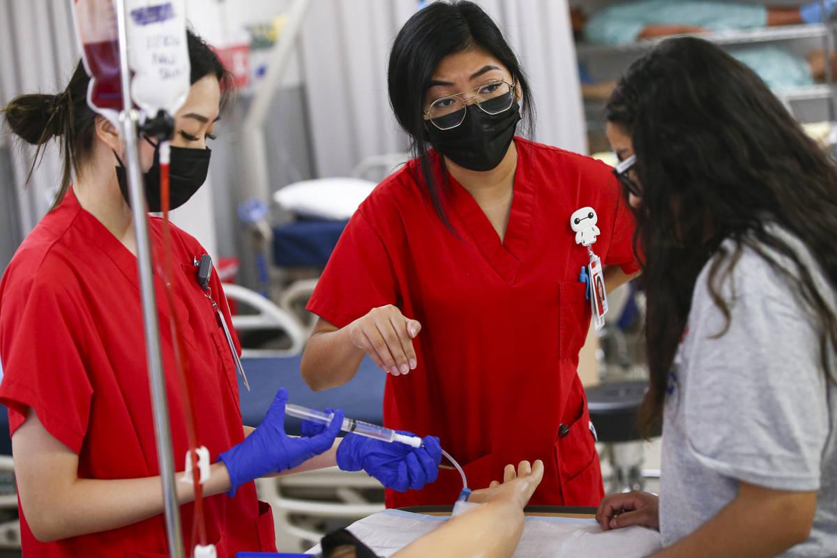 UNLV nursing students Susan Oh, left, and Kiara Andrada, center, show Camila Puente, a junior a ...