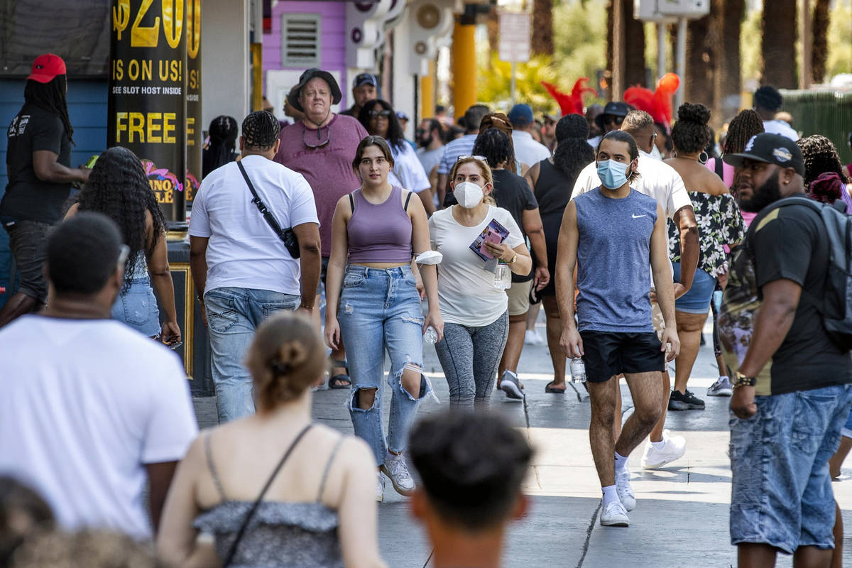People walk along the Strip near The Venetian, most not wearing masks, on Friday, July 16, 2021 ...