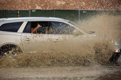 Cars move through a flooded portion of Buffalo Drive near Post Road in Las Vegas on Wednesday, ...