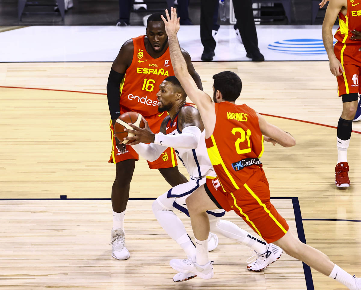 United States guard Damian Lillard, center, drives the ball under pressure from Spain forward U ...