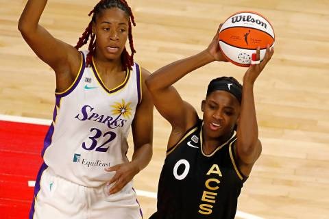 Las Vegas Aces guard Jackie Young (0) looks to pass against Los Angeles Sparks guard Bria Holme ...