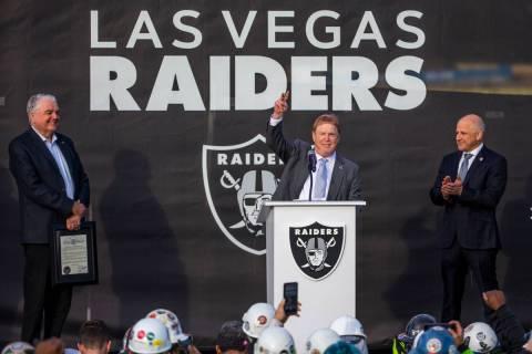 Governor Steve Sisolak, left, looks to Las Vegas Raiders owner Mark Davis who addresses the cro ...