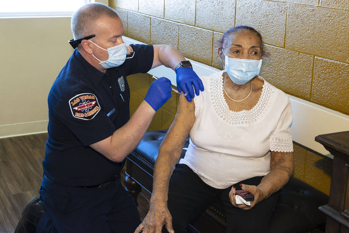 Chris Racine of Las Vegas Fire Rescue administers a COVID-19 vaccine to the Stella Fleming Towe ...