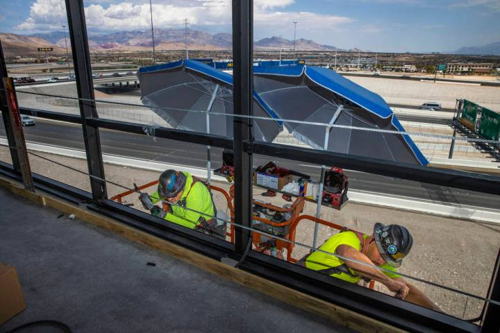 Eric Oudeman, left, and Tacoma McCormick of Quantum Glass and Mirror work the exterior atop Off ...