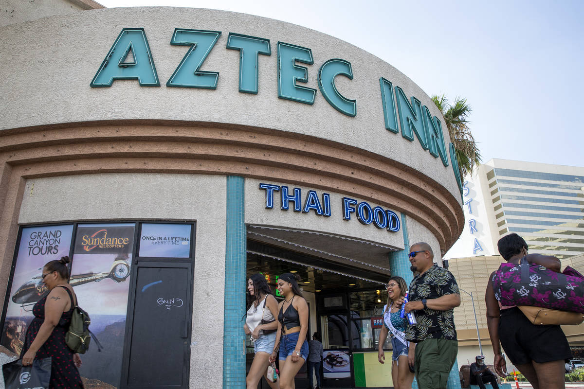 Pedestrians walk past Aztec Inn Casino, a property for sale on Las Vegas Boulevard, on Tuesday, ...