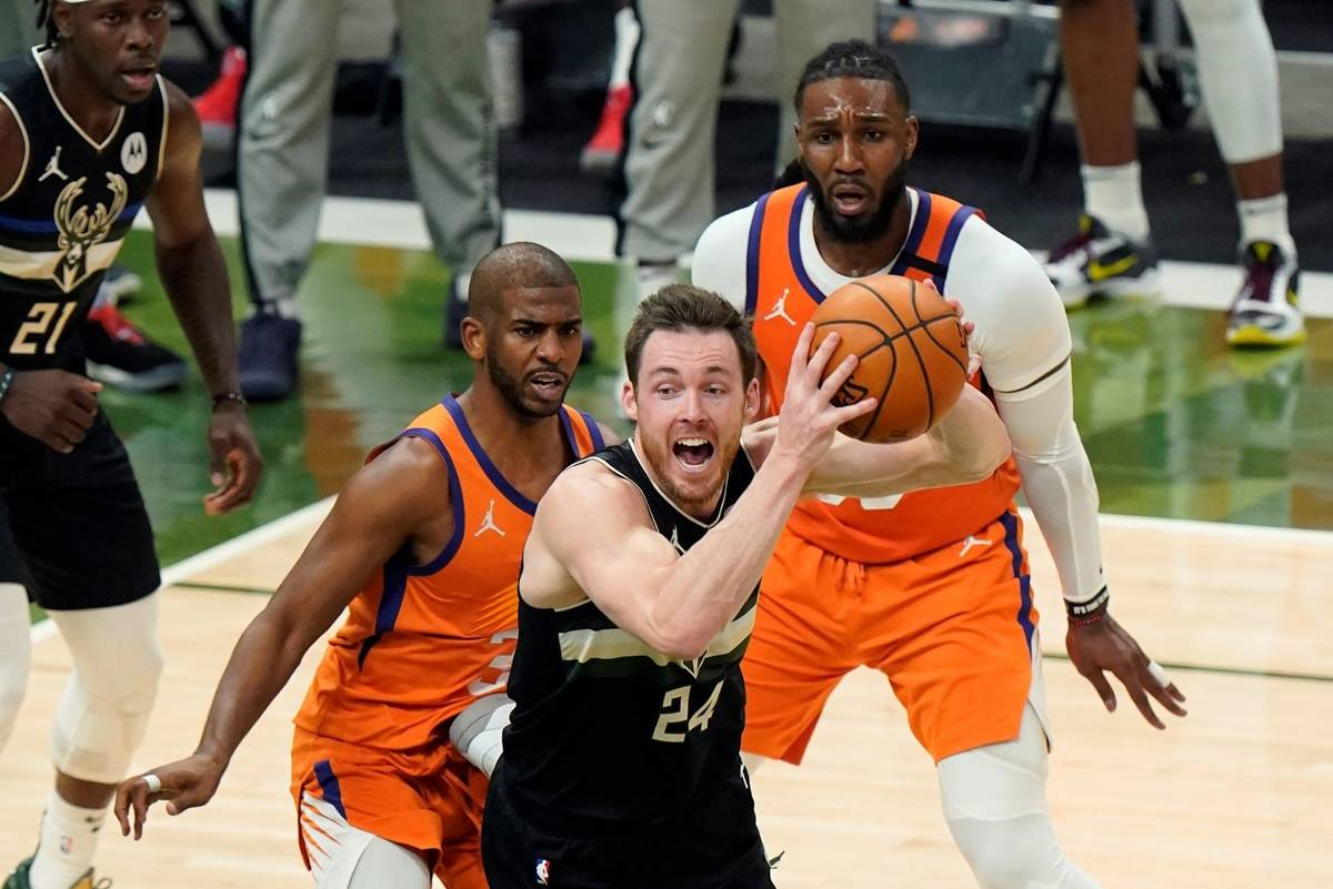 Milwaukee Bucks guard Pat Connaughton (24) looks to pass under pressure from Phoenix Suns guard ...