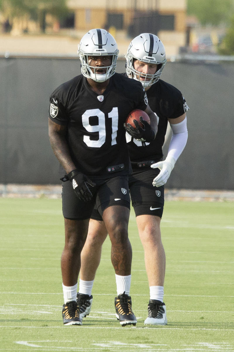 Raiders defensive ends Yannick Ngakoue (91) run a drill with Maxx Crosby (98) during their NFL ...