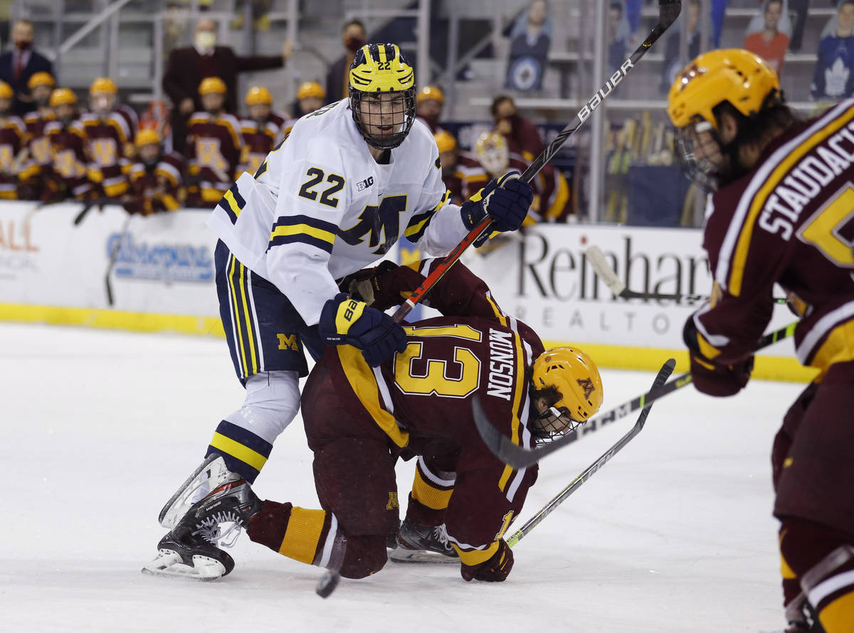 FILE - In this Dec. 8, 2020, file photo, Michigan's Owen Power (22) watches the puck while work ...