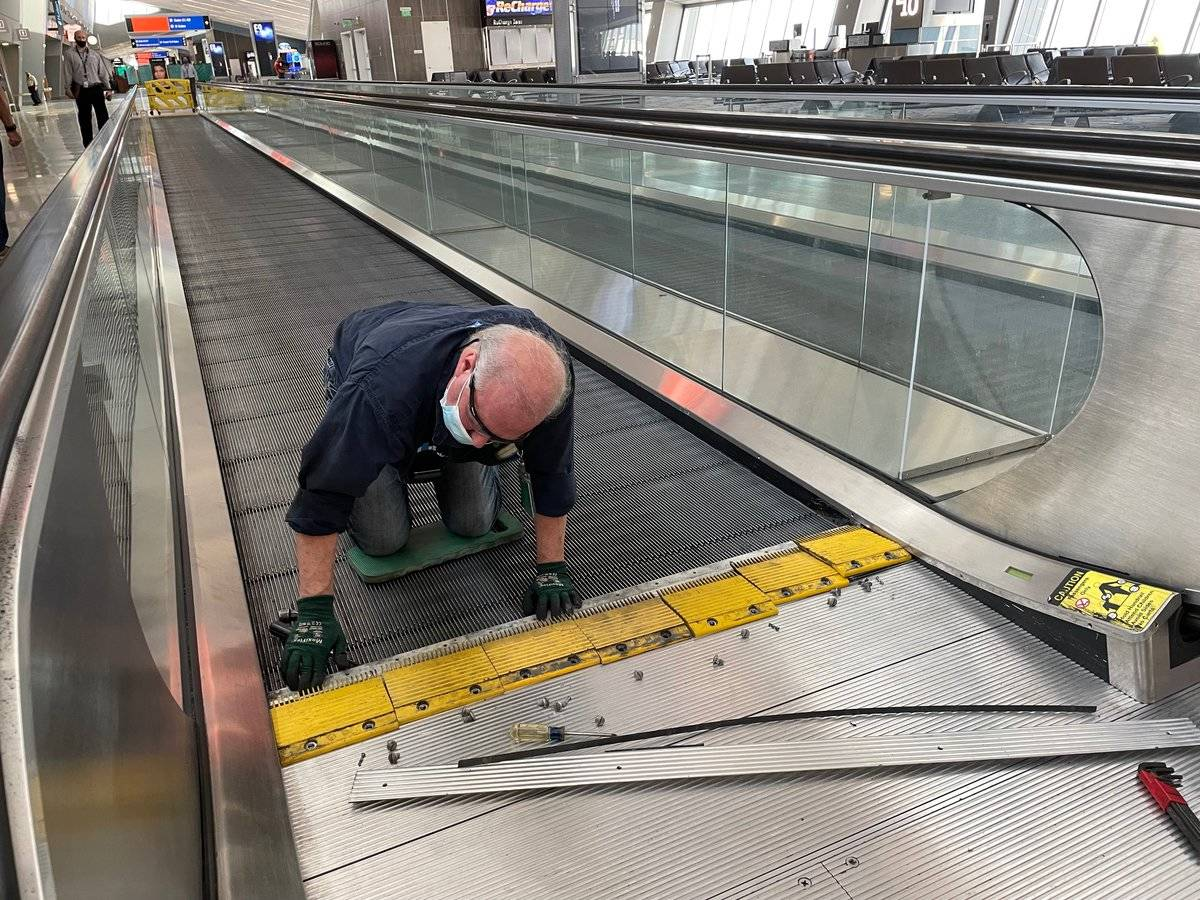 A worker preps a moving walkway at the E Gates in Terminal 3 of McCarran International Airport, ...