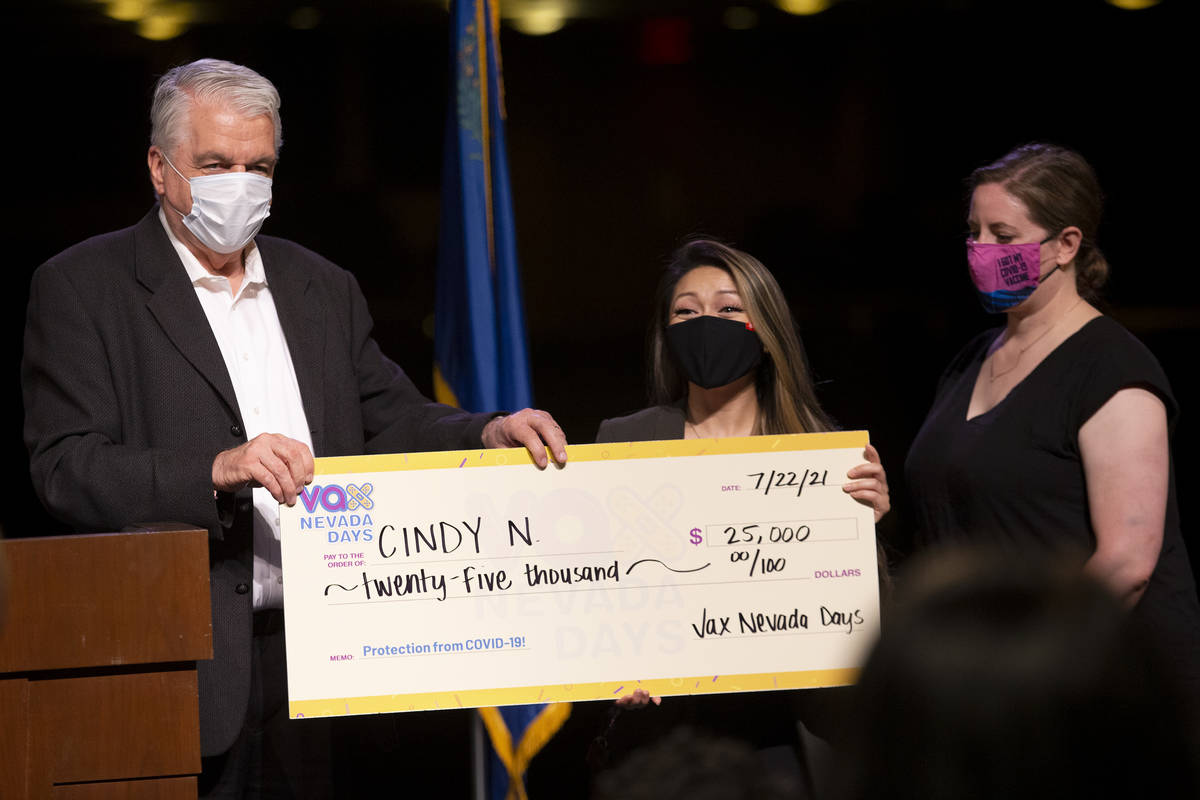Gov. Steve Sisolak and Immunize Nevada hand over a check to Cindy N. for $25,000 during the ann ...