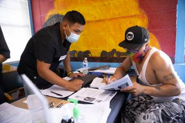 Francisco Ortiz, left, with Impact Health, assists Dino Poston with his intake information for ...