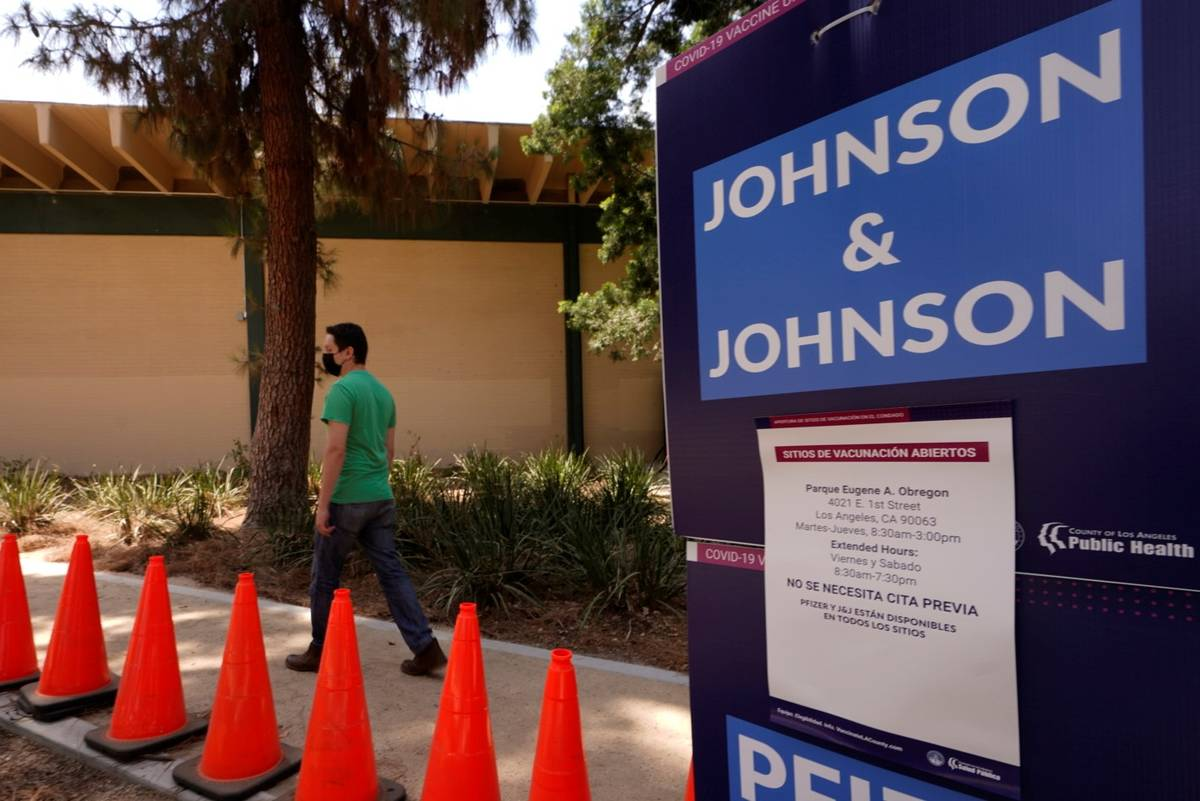 Carlos Arrendondo arrives for his appointment to get vaccinated, as banners advertise the avail ...