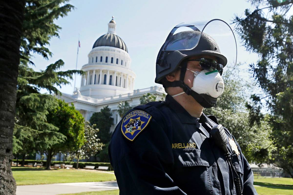 California Highway Patrol Officer S. Arellano wears a face mask at the the state Capitol in Sac ...