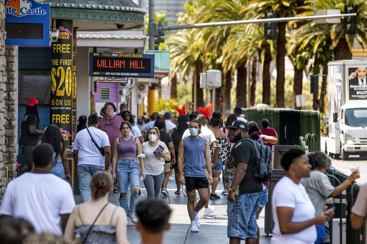 People walk along the Strip near The Venetian, most not wearing masks anymore on Friday, July 1 ...