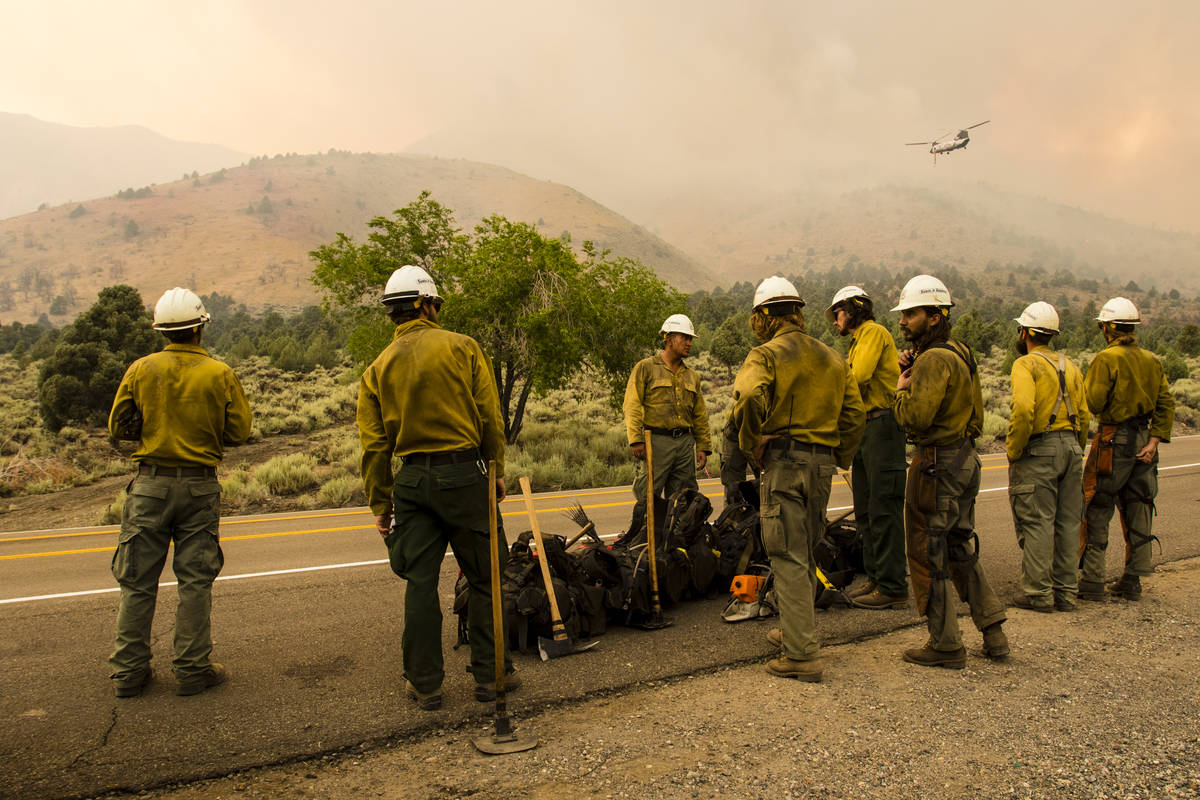 A Santa Fe Hotshots crew gathers while battling the Tamarack Fire around Topaz Lake, Nev., Frid ...