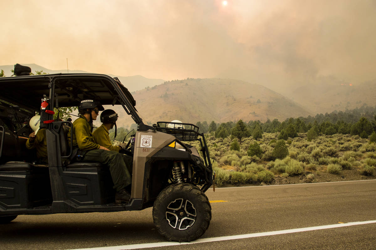 A Santa Fe Hotshots crew drives around Topaz Lake, Nev., Friday, July 23, 2021, as battling th ...