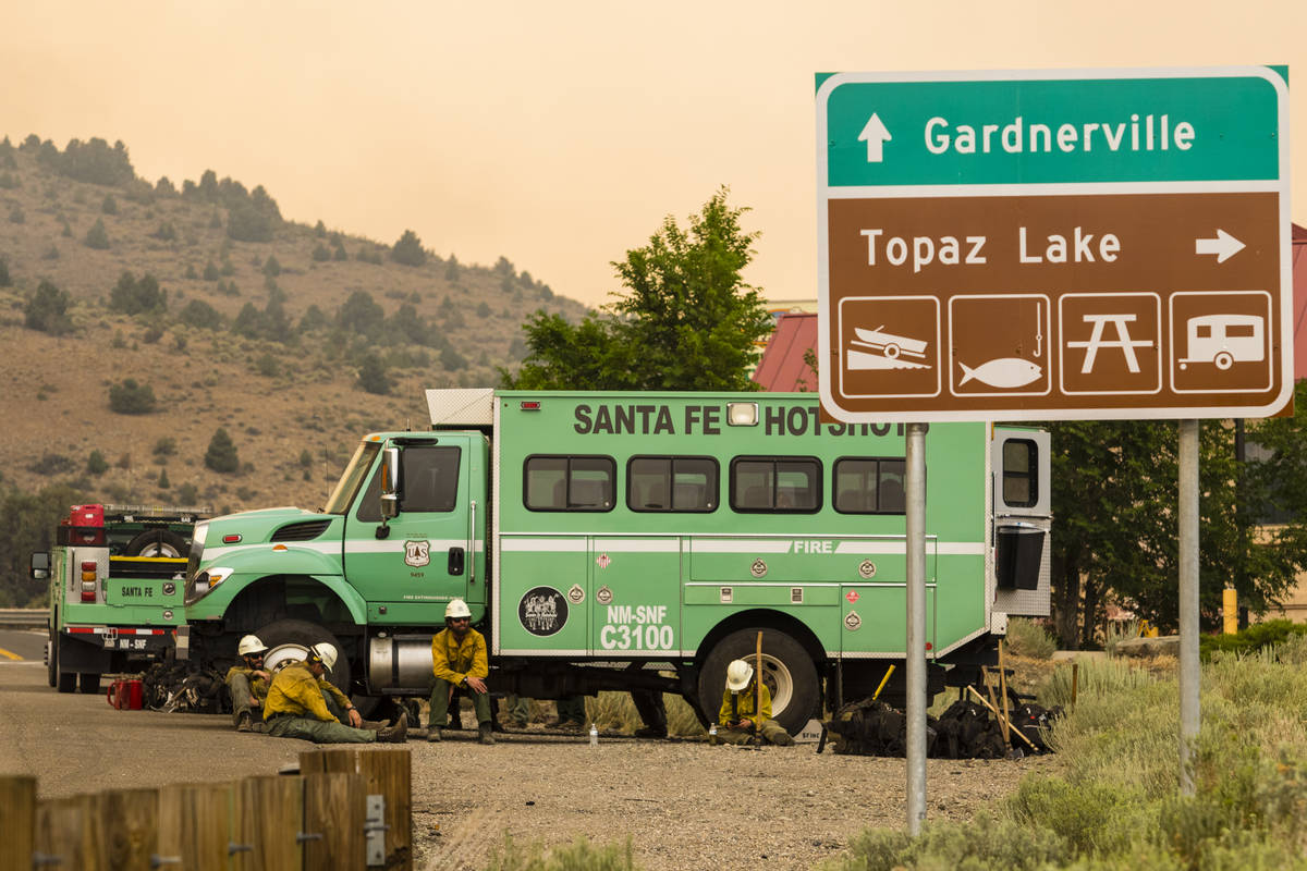 A Santa Fe Hotshots crew is seen in Topaz Lake, Nev., Friday, July 23, 2021, while battling the ...