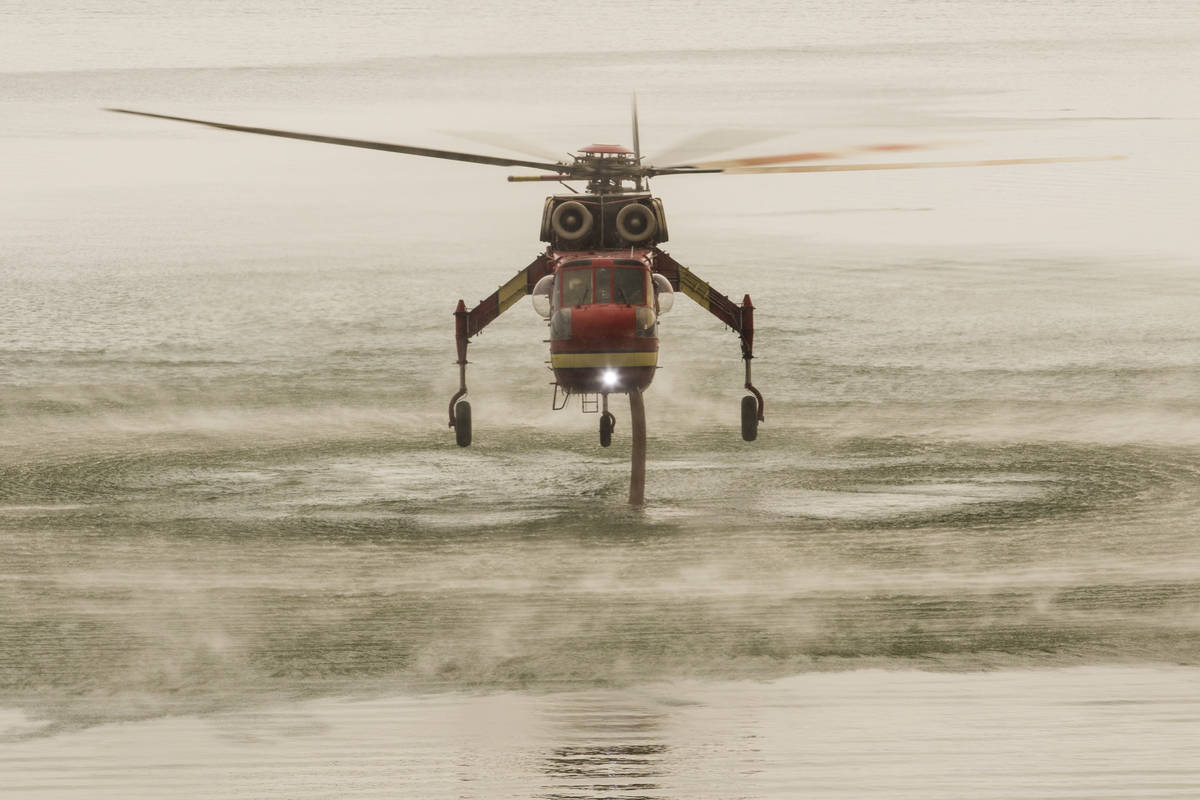 A firefighting helicopter is seen at Topaz Lake, in Nevada, Friday, July 23, 2021, while the T ...