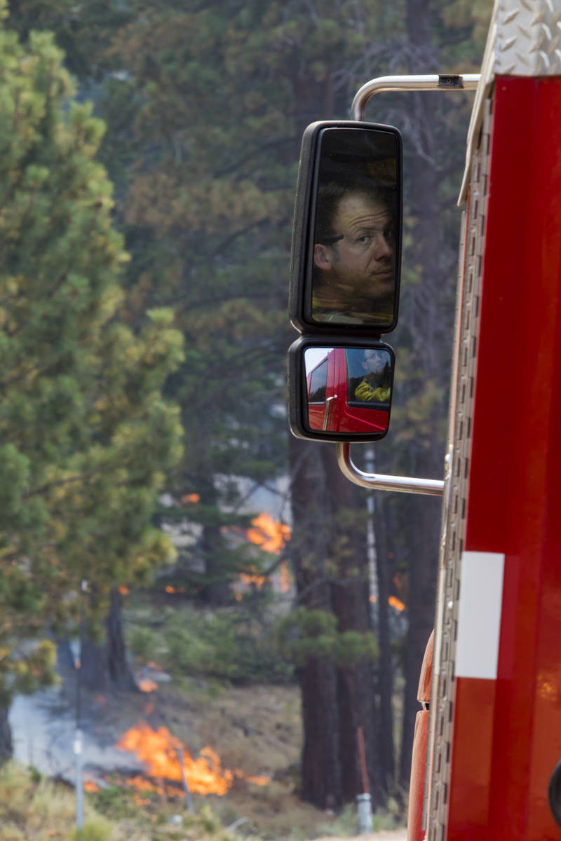 A So-Cal fireman is reflected in a side mirror around California State Route 88 near Alpine Vil ...