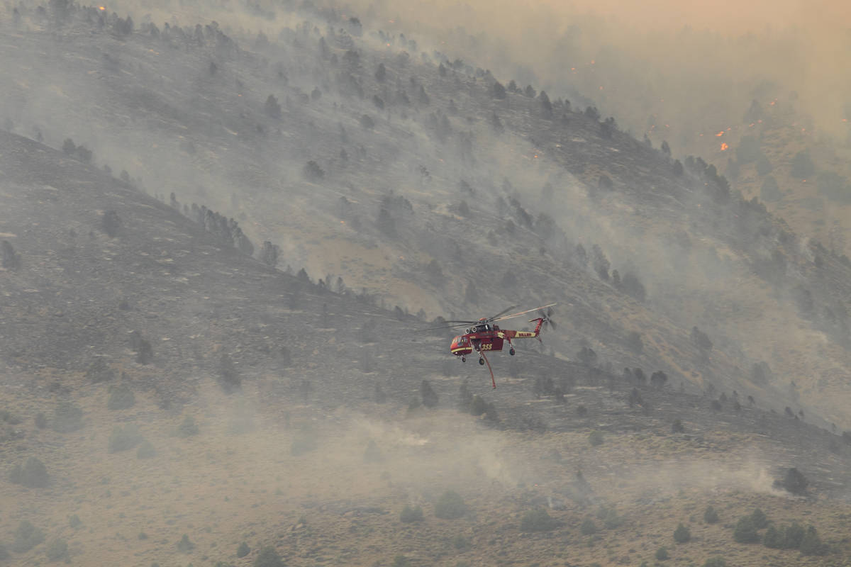 A firefighting helicopter flies as the Tamarack Fire burns around Topaz Lake, Nev., Friday, Jul ...