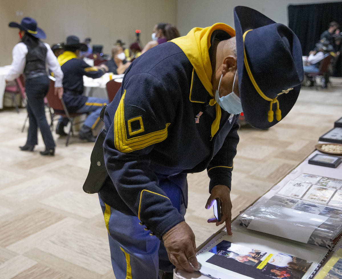 Mitchell Sayles, a member of the Buffalo Soldiers, pages through a scrapbook during an event fo ...