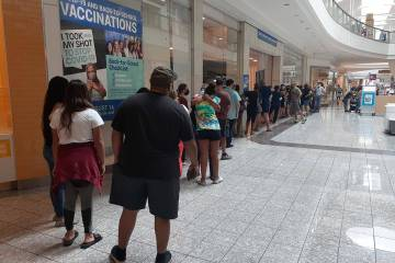 Several dozen people line up for the opening of a coronavirus vaccination clinic at the Galleri ...