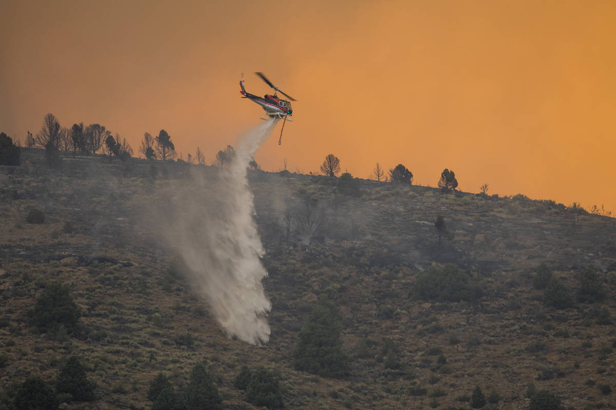 A firefighting helicopter drops water as the Tamarack Fire burns around Topaz Lake, Nev., Frida ...