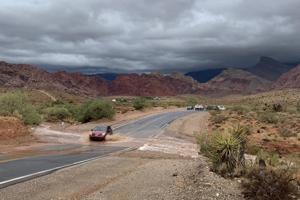 A vehicle drives through a flooded section of Calico Basin Road near Red Rock Canyon National C ...