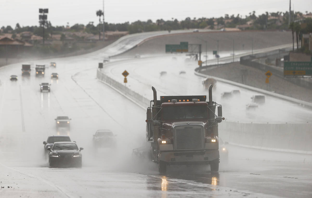 Vehicles travel through wet road conditions going northbound on the 215 Beltway in the Summerli ...