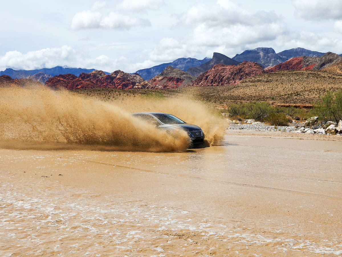 A car drives over a flooded portion of Blue Diamond Road near Red Rock National Conservation Ar ...