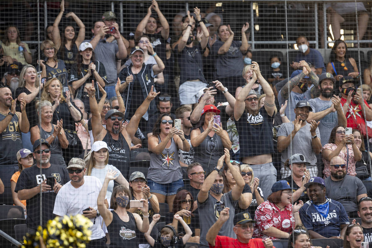 Fans cheers for the players during a charity softball game involving teammates from the Vegas G ...