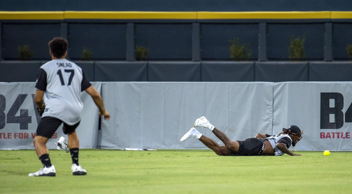 Las Vegas Raiders Damon Arnette (20, right) misses a long fly ball as teammate Willie Snead IV ...