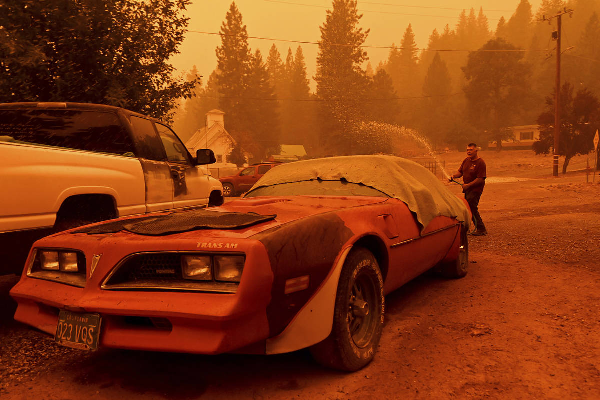 William Deal wets down his 1977 Trans Am as the Dixie Fire approaches Crescent Mills in Plumas ...
