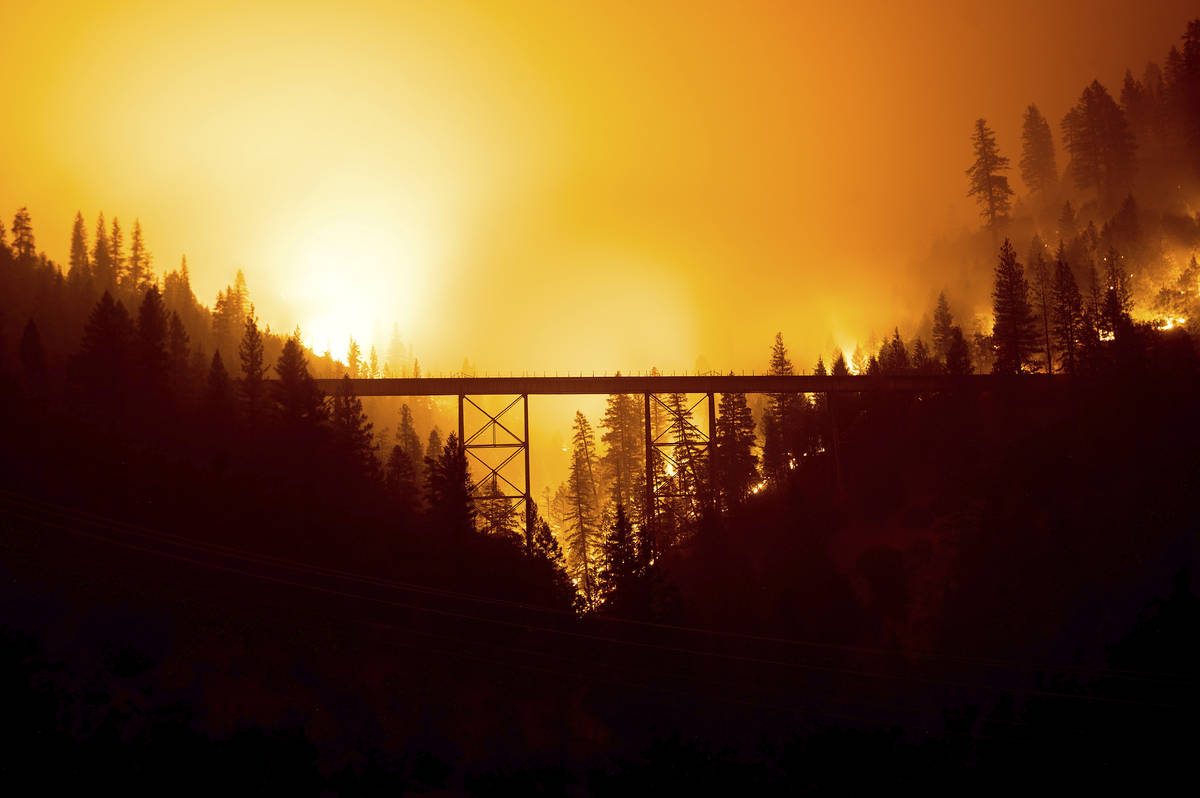 Seen in a long exposure photograph, the Dixie Fire burns behind a bridge in Plumas County, Cali ...