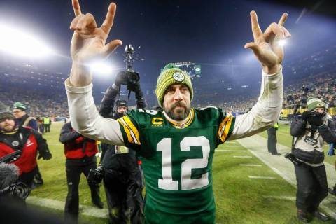 Green Bay Packers' Aaron Rodgers celebrates as he walks off the field after an NFL divisional p ...