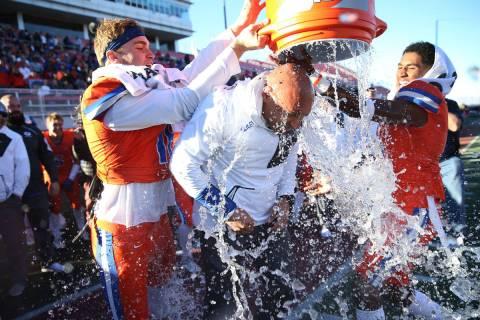 Bishop Gorman's head football coach Kenny Sanchez, center, gets a Gatorade (water) shower by hi ...
