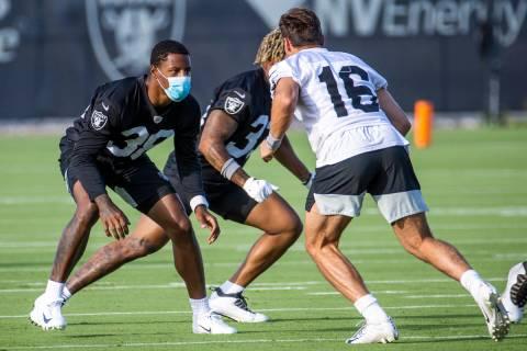 Raiders cornerback Rasul Douglas (38, left) wears a mask while defending against teammate wide ...
