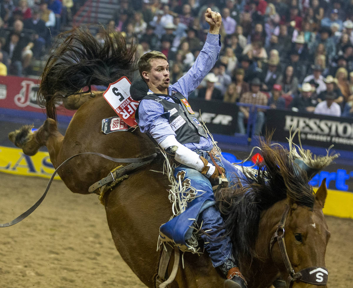 Orin Larsen of Inglis, Manitoba, digs into the saddle in Bareback Riding during the tenth go ro ...