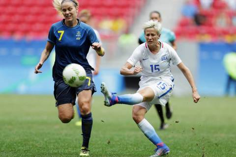 In this Friday, Aug. 12, 2016, file photo, United States' Megan Rapinoe, right, kicks the ball ...