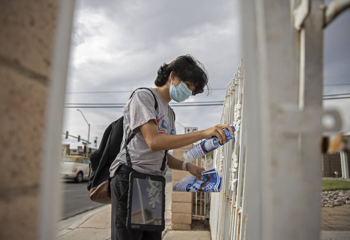 Jacinto Alfaro, a volunteer with the nonprofit Mi Familia Vota, posts COVID-19 vaccine informat ...