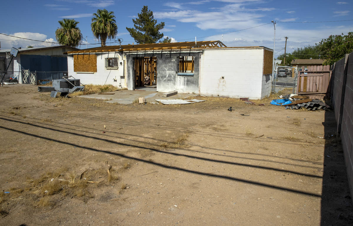 Boarded up windows on the exterior of a burned-out house that is currently listed for sale alon ...
